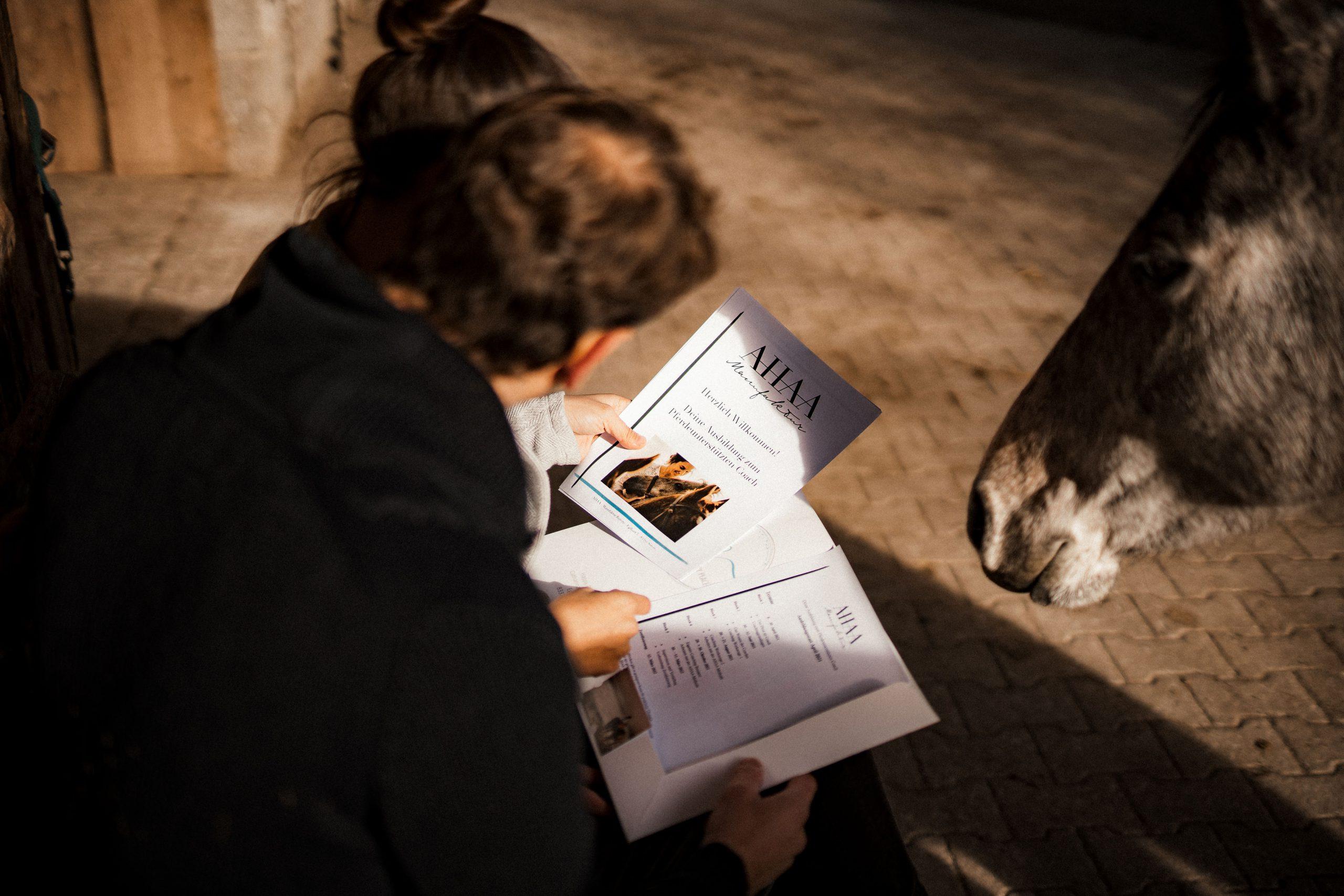 Zwei Menschen und ein Pferd studieren die Unterlagen der AHAA Manufaktur Bayern