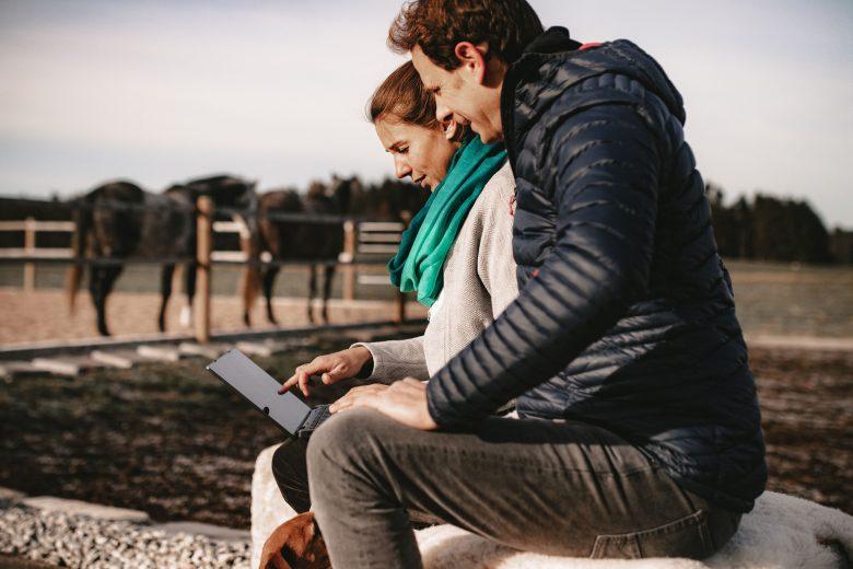 Catharina und Helwig Falch sitzen mit Laptop an Reitplatz